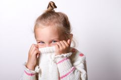 Portrait of a charming little girl in beige sweate. Hides his nose. child playing peekaboo.  hiding inside the neck of her pullover while smiling at the camera Royalty Free Stock Image