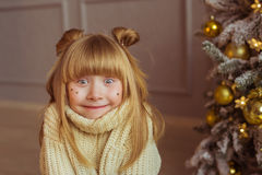 Portrait of a charming little girl in beige sweater makes faces in Christmas Royalty Free Stock Photo
