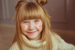 Portrait of a charming little girl in beige sweater smiles at home Royalty Free Stock Photos