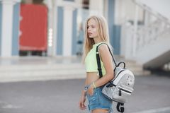 Young beautiful blonde woman with a bag in his hand, street summer outdoors royalty free stock image