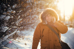 Portrait of the charming man who is smiling and talking on the phone in the winter cold day at sunset, dawn. Stock Image