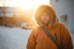 Portrait of the charming man who is smiling and talking on the phone in the winter cold day at sunset, dawn. Royalty Free Stock Photography