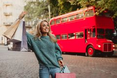 Beautiful woman waving hand while standing on the street royalty free stock photography