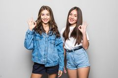 Portrait of charming mixed race girls with beaming smiles long hair gesturing ok sign with fingers isolated on gray background. royalty free stock photos