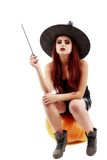 Portrait of a charming red-haired witch holding pumpkin . Hallow Royalty Free Stock Photos