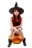 Portrait of a charming red-haired witch holding pumpkin with red Royalty Free Stock Images