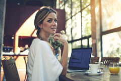 Portrait of charming smiling businesswomen posing while resting after work on her portable laptop computer during coffee break Royalty Free Stock Image