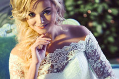 Portrait of charming woman in wedding dress. The girl bride sits in a chair Royalty Free Stock Photography