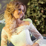 Portrait of charming woman in wedding dress. The girl bride sits in a chair Royalty Free Stock Image