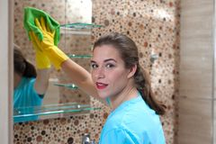 Charming woman doing cleaning. Portrait of charming young female employee of cleaning company in rubber gloves wiping furniture in bathroom royalty free stock photography