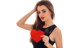 Portrait of a charming young girl that holds a Valentine Sweetheart and looks down Royalty Free Stock Photo