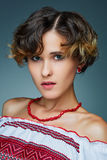 Portrait charming young lady with short wavy hair in embroidery. Royalty Free Stock Photography