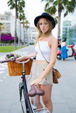 Portrait of a charming young woman dressed in trendy clothing rest after riding around the city on her vintage bike Royalty Free Stock Photo