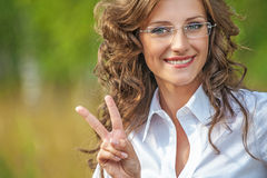 Portrait charming young woman glasses shows sign victory Stock Photos