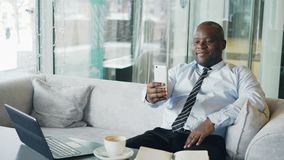 Happy African American businessman taking a selfie on his smartphone and showing a thumb up gesture while drinking stock footage