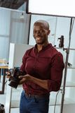Portrait of cheerful african american photographer with photo camera in hands looking at camera. In studio Royalty Free Stock Images