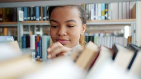 Portrait of cheerful African American teenager choosing books in school library. Touching textbooks smiling. Education, people and youth culture concept stock footage