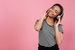 Portrait of a cheerful african woman listening music with headphones. Portrait of a smiling cheerful african woman listening music with headphones isolated over royalty free stock photo