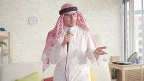 Cheerful Arab man in traditional clothes singing in karaoke microphone at home. Portrait of cheerful Arab man in traditional clothes singing in karaoke stock video footage