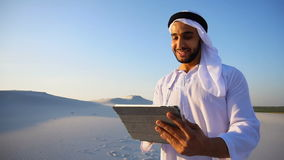 Portrait of cheerful Arab tourist who prints notes on gadget, standing among big desert on summer day. Portrait of stately Arabian Sheikh man who with smile on stock video
