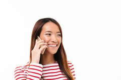 Portrait of a cheerful asian girl talking on mobile phone. Portrait of a cheerful pretty asian girl talking on mobile phone while standing isolated over white Royalty Free Stock Images