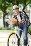 Getting ready for exams. Portrait of cheerful Asian university student leaning on bicycle when reading a book Stock Image