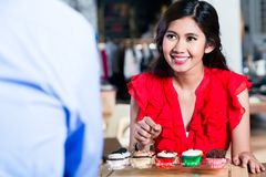 Portrait of a cheerful Asian woman ordering cupcakes in a cool cafe royalty free stock photo