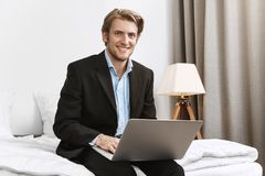 Portrait of cheerful attractive bearded company director in stylish black suit smiling brightfully, working on laptop royalty free stock image