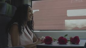 Woman going on vacation sitting next the train window having conversation and smiling with roses as present during the journey stock video