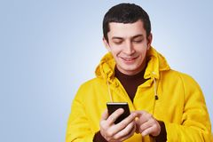 Portrait of cheerful attractive young man uses modern cell phone, surf social networks, glad read pleasant comments on his photo, Stock Images