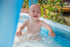Portrait of cheerful baby boy playing in inflatable swimming pool.  stock image