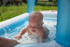 Portrait of cheerful baby boy playing in inflatable swimming pool.  royalty free stock photos