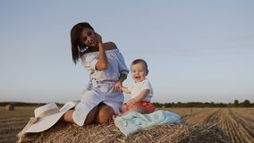 Portrait of a cheerful baby and his mother sitting on a bale with straw in the field. Young woman with her son walking stock footage
