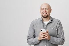 Portrait of cheerful bald caucasian man with beard holding smartphone while recalling something funny, looking aside and stock image