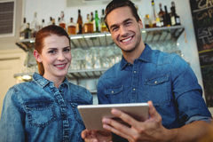 Portrait of cheerful baristas with digital tablet at cafe. Portrait of cheerful young baristas with digital tablet at cafe Royalty Free Stock Photos