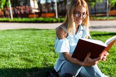 Portrait of a cheerful beautiful student girl sitting outdoors o stock photo