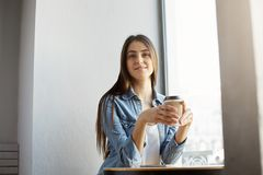 Portrait of cheerful beautiful woman with dark hair and stylish clothes sitting in cafeteria, smiling, drinking coffee Royalty Free Stock Photos