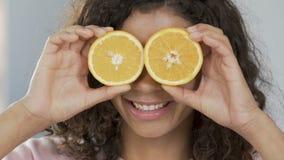 Portrait of cheerful biracial woman applying halves of orange to eyes, optimism. Stock footage stock footage