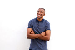 Cheerful black guy with arms crossed and looking away against white background. Portrait of cheerful black guy with arms crossed and looking away against white royalty free stock images