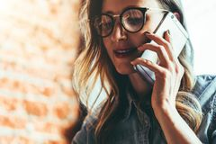 Portrait of cheerful blogger girl in glasses sitting in cafe,talking on phone. Entrepreneur has telephone conversations. Portrait of cheerful blogger girl in royalty free stock photo