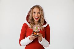 Portrait of a cheerful blonde woman. Dressed in red New Year costume standing over white background, holding snowball stock photography
