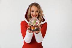 Portrait of a cheerful blonde woman. Dressed in red New Year costume standing over white background, holding snowball royalty free stock photography