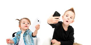 Portrait of cheerful boy and cute girl taking selfie on mobile phone stock photography