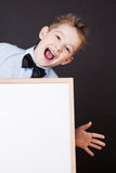 Portrait of cheerful boy pointing on white banner Royalty Free Stock Photography