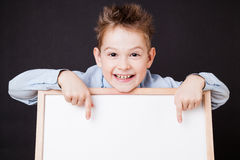 Portrait of cheerful boy pointing on white banner Stock Photos