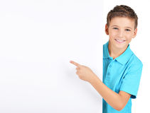 Portrait of  cheerful boy pointing on white banner. Isolated on white background Royalty Free Stock Images
