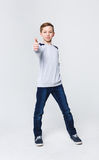 Portrait of cheerful boy showing thumbs up gesture. Full length portrait of cheerful boy showing thumb up gesture over white studio background. Happy smiling boy Stock Photo