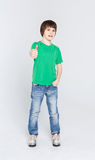 Portrait of cheerful boy showing thumbs up gesture. Full length portrait of cheerful boy showing thumb up gesture over white studio background. Happy smiling boy Stock Images