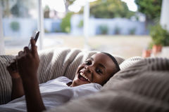 Portrait of cheerful boy using mobile at home Stock Image
