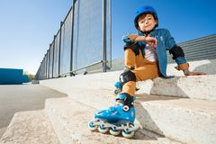 Boy wearing roller blades sitting on the stairs Stock Images